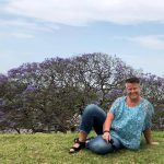 Annica vid ett blommande jakaranda-träd